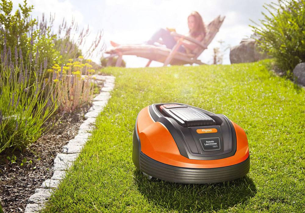 Flymo 1200 R robotic lawnmower cutting grass in sunny garden